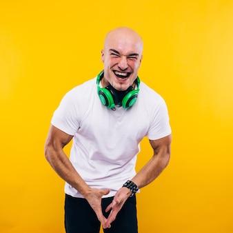 Homme chauve en t-shirt blanc sur mur jaune