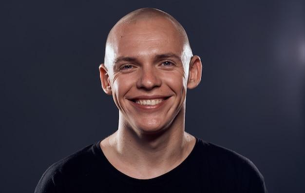 Un homme chauve avec une tête percée dans un pull noir émotions