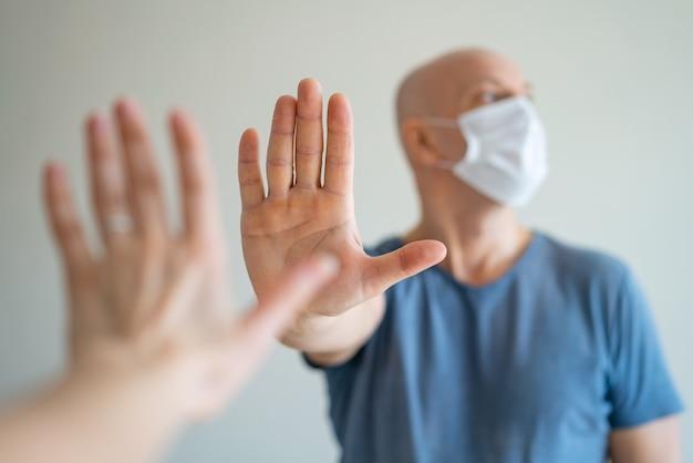Un homme chauve tient un masque médical dans ses mains, son autre main tendue en signe de protestation