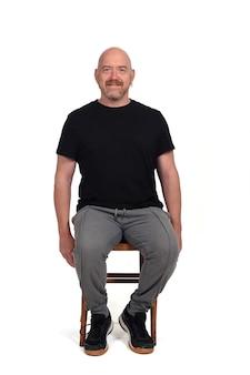 Homme chauve avec des vêtements de sport assis sur fond blanc
