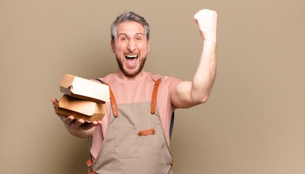 Homme de chef d'âge moyen avec des hamburgers. concept de barbecue