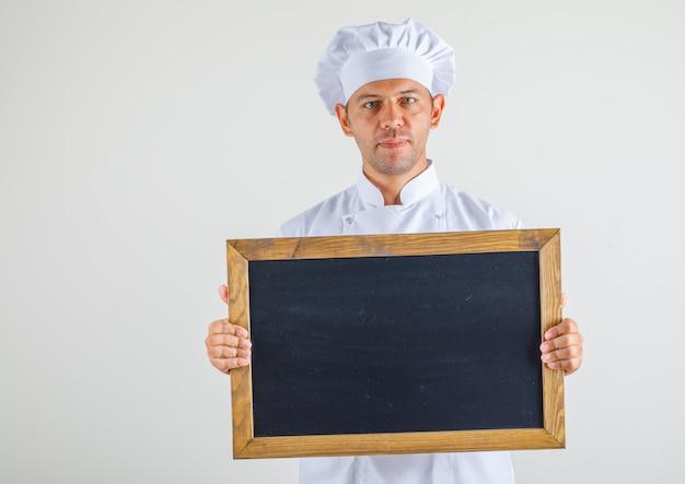 Homme chef cuisinier en chapeau et uniforme tenant tableau noir