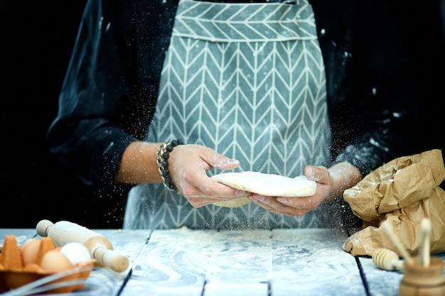 L'homme, le chef cuisinier jette la pâte, volant, se congelant en mouvement.