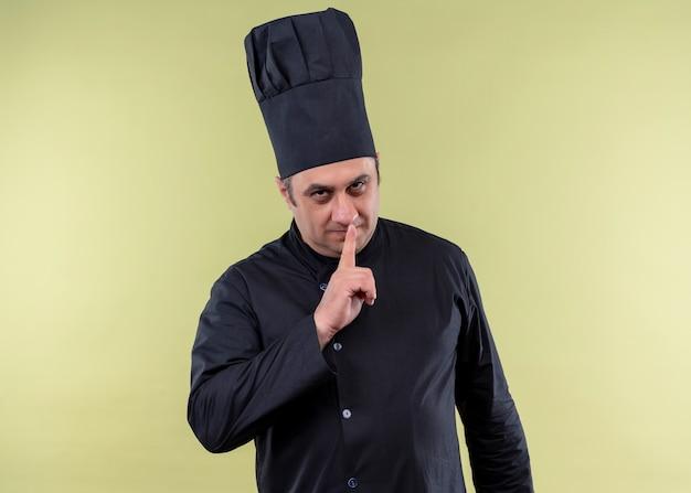 Homme chef cuisinier portant l'uniforme noir et chapeau de cuisinier faisant le geste de silence avec le doigt sur les lèvres regardant la caméra avec un visage sérieux debout sur fond vert
