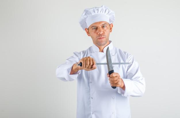 Homme chef cuisinier tenant des couteaux de cuisine en uniforme et chapeau et à la confiance