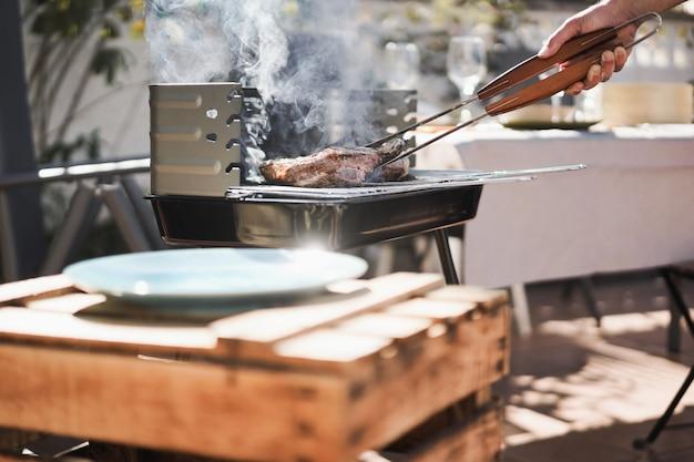 Homme de chef faisant cuire la viande au dîner à la maison de barbecue extérieur au jardin d'arrière-cour