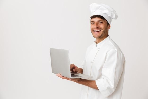 Homme de chef isolé sur mur blanc à l'aide d'un ordinateur portable.