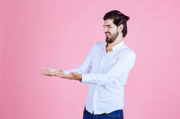 L'homme en chemise blanche a l'air confus et essaie de s'expliquer en utilisant des gestes de la main.