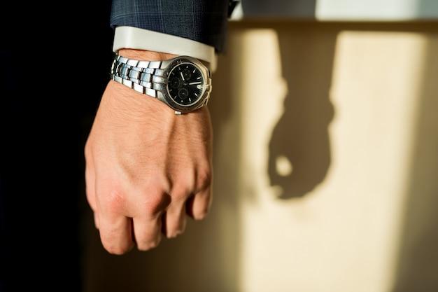 Homme en chemise blanche et costume sombre avec montre de luxe de marque