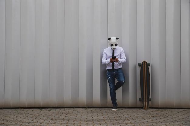 Homme en chemise blanche, cravate et masque d'ours panda discutant avec un smartphone. espace pour le texte