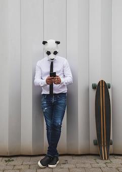 Homme en chemise blanche, cravate et masque d'ours panda discutant avec un smartphone