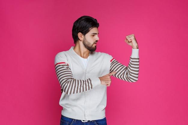 Homme en chemise blanche démontrant ses muscles et sa puissance de bras.