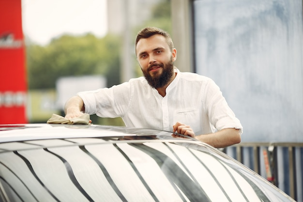 Homme en chemise blanche essuie une voiture dans un lave-auto