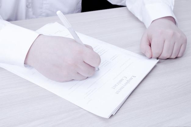 Un homme en chemise blanche est assis à une table et signe un contrat de travail