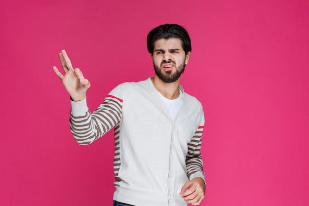 Homme en chemise blanche faisant signe de main ok ou perfection.