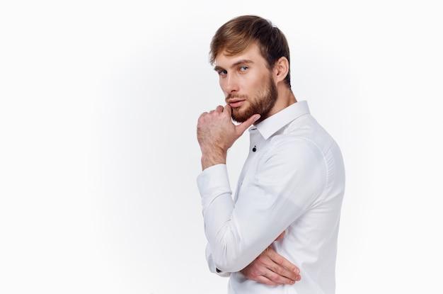 Homme en chemise blanche gesticulant avec les mains sur la lumière