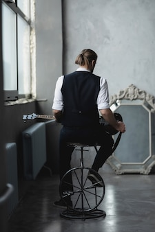 Un homme en chemise blanche et gilet est assis et regarde dans son reflet dans le miroir et joue de la guitare
