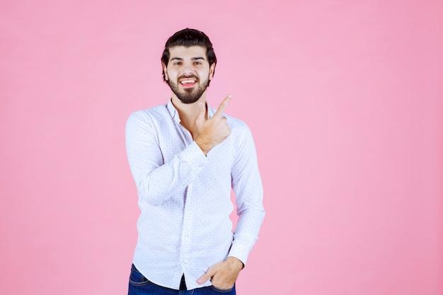 Homme en chemise blanche levant la main pour attirer l'attention ou montrer quelque chose.