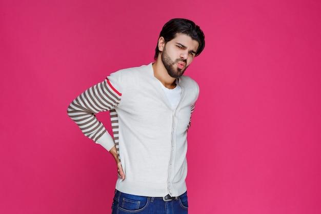 L'homme en chemise blanche a mal au dos et tient sa taille.