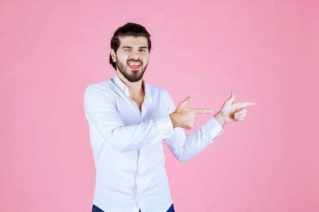Homme en chemise blanche montrant le côté droit avec émotions.