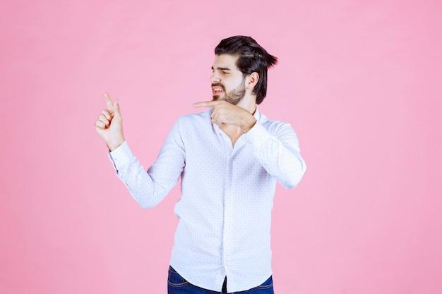 Homme en chemise blanche montrant le côté gauche avec émotions.