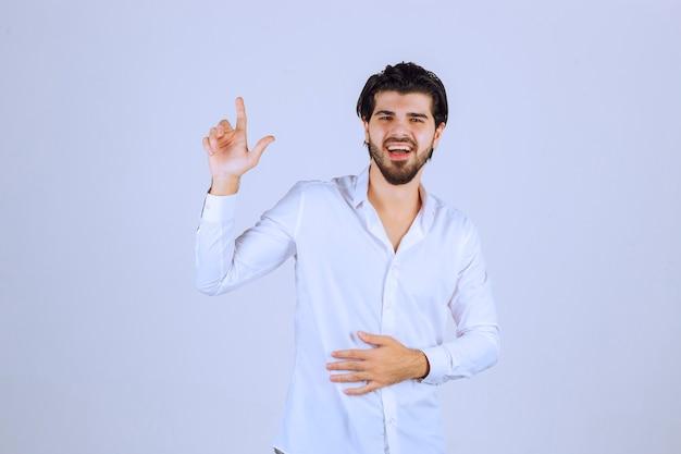 Homme en chemise blanche montrant quelque chose au-dessus et souriant.