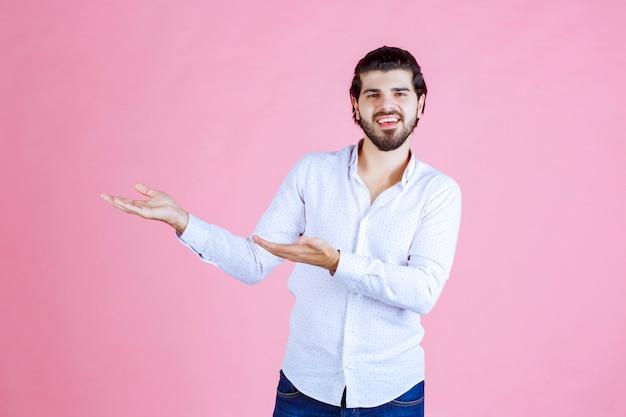Homme en chemise blanche montrant quelque chose dans sa main.