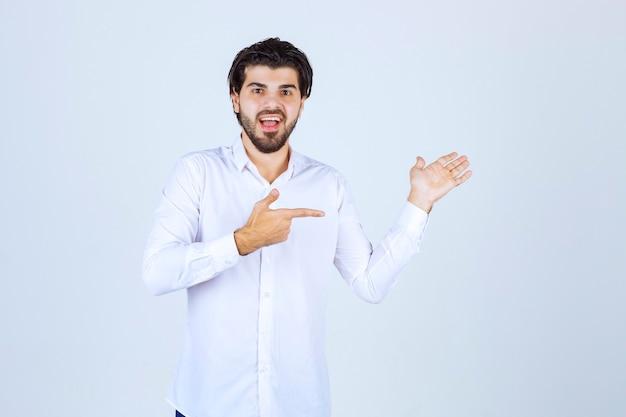 Homme en chemise blanche montrant quelque chose sur la droite.
