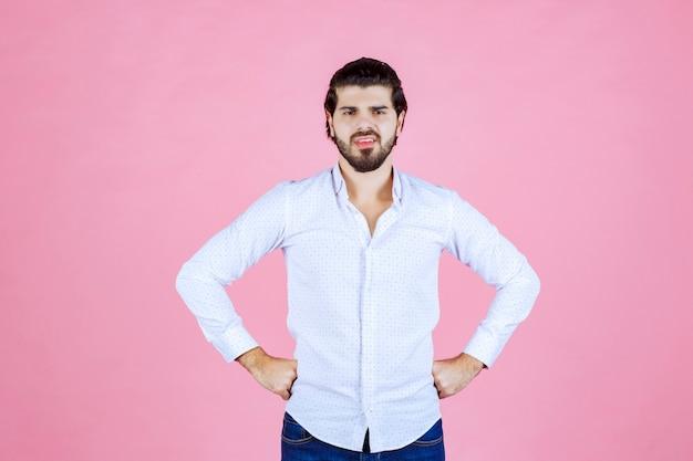 L'homme en chemise blanche pense ou a l'air pensif.