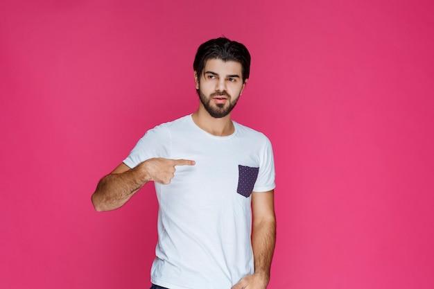 Homme en chemise blanche pointant sur lui-même.