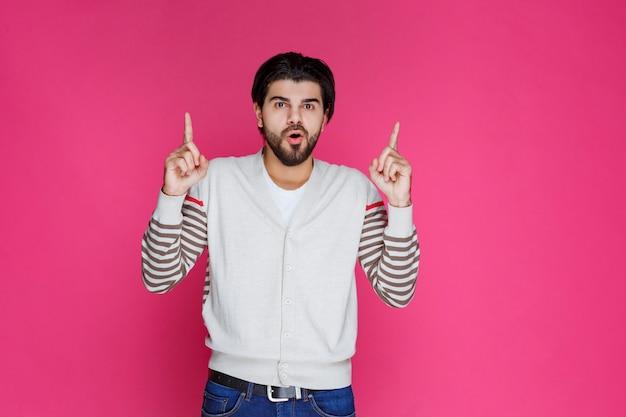 Homme en chemise blanche pointant et présentant quelque chose au-dessus de sa tête.