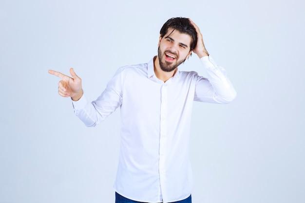 Homme en chemise blanche pointant quelque part sur la gauche avec des émotions de visage.