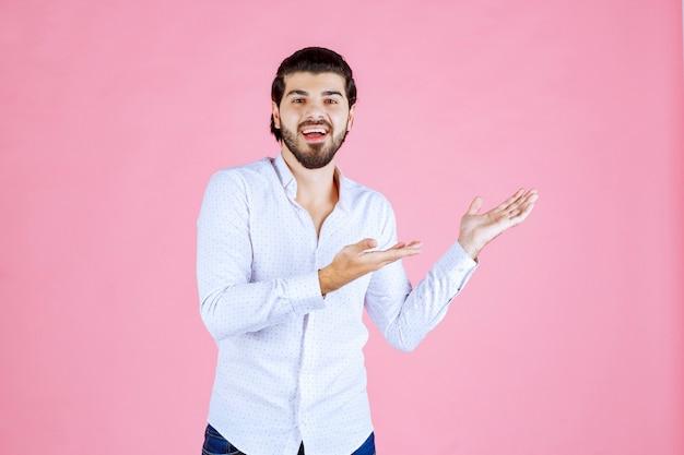 Homme en chemise blanche pointant vers le côté droit.