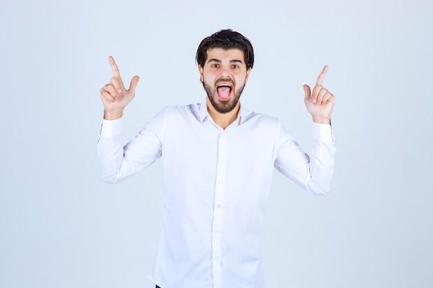 Homme en chemise blanche pointant vers le haut.