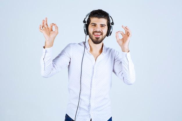 Homme en chemise blanche portant des écouteurs et profitant de la musique