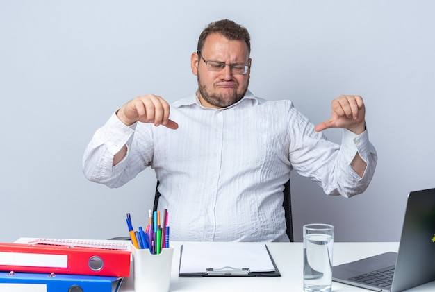 Homme en chemise blanche portant des lunettes assis à la table avec des dossiers de bureau et un presse-papiers regardant l'écran d'un ordinateur portable montrant les pouces vers le bas étant mécontent sur un mur blanc travaillant au bureau