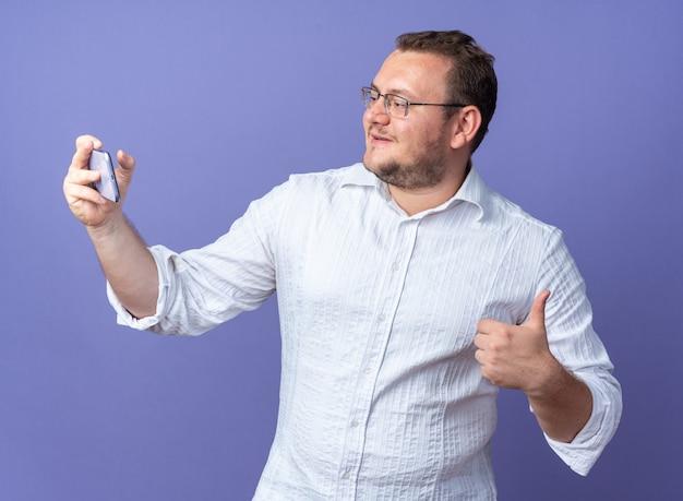 Homme en chemise blanche portant des lunettes tenant un smartphone ayant un appel vidéo heureux et positif montrant les pouces vers le haut debout sur le mur bleu