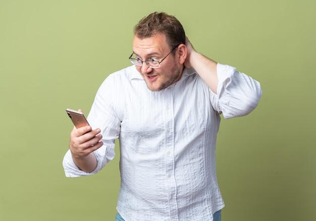 Homme en chemise blanche portant des lunettes tenant un smartphone en le regardant étonné et surpris debout sur le vert