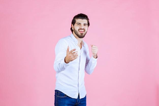 Homme en chemise blanche remarquant et pointant du doigt la personne devant.