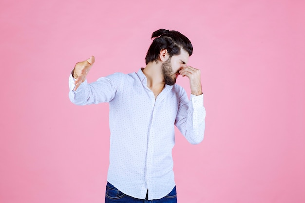 Homme en chemise blanche retenant son souffle alors qu'il sent une mauvaise odeur.