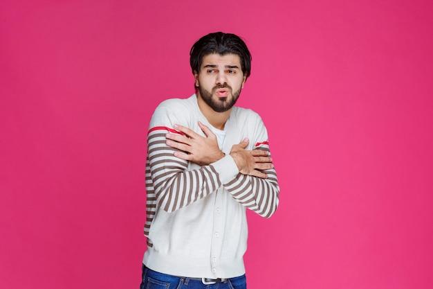 Homme en chemise blanche sensation de froid et de maux de gorge.