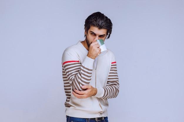 Homme en chemise blanche tenant et posant avec une tasse de café.