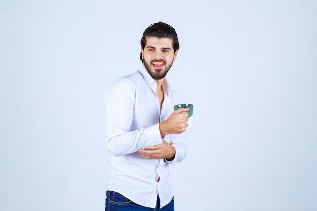 Homme en chemise blanche tenant une tasse de café et en profitant
