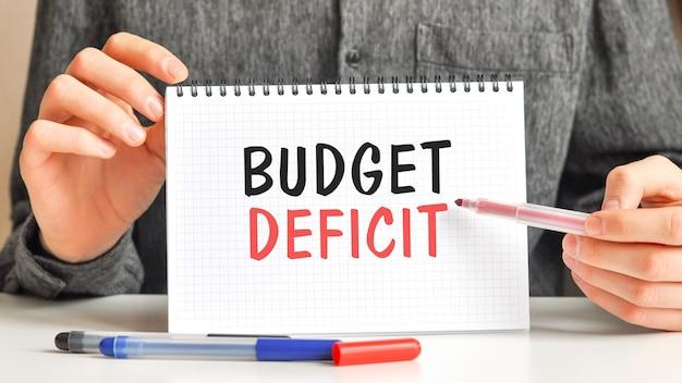 Un homme en chemise blanche tient un morceau de papier avec le texte: déficit budgétaire