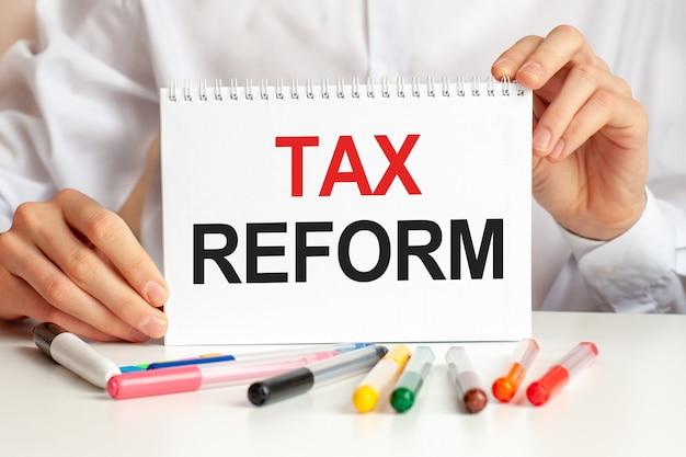 Un homme en chemise blanche tient un morceau de papier avec le texte: réforme fiscale