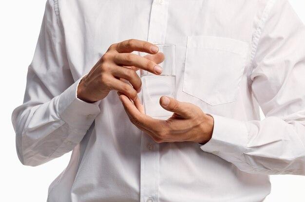 Un homme en chemise blanche tient un verre d'eau à la main sur un mur lumineux.