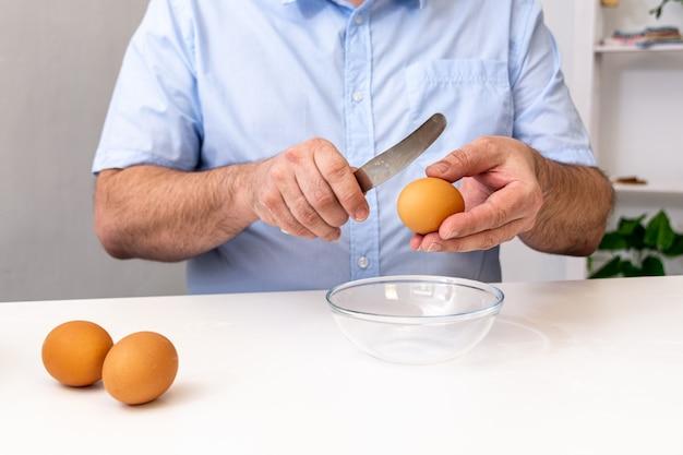 Un homme en chemise bleue casse un œuf avec un couteau dans une tasse transparente