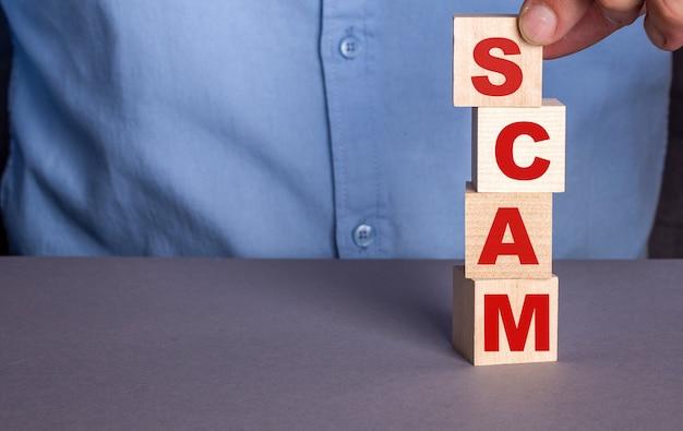Un homme en chemise bleue compose le mot scam à partir de cubes en bois verticalement