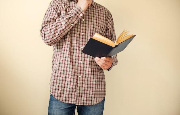 Homme en chemise à carreaux marron lisant un livre