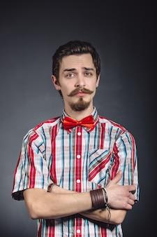Homme en chemise à carreaux et noeud papillon en studio